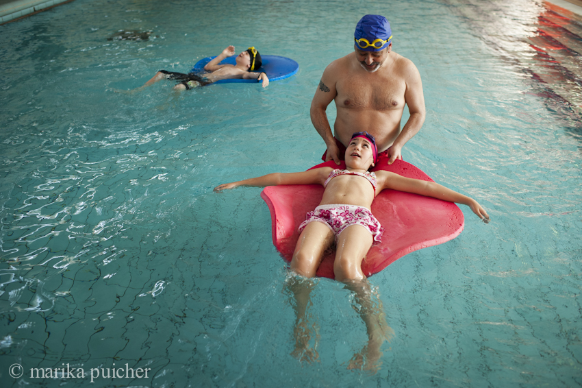 """Eli with her father Miguel and her younger brother Nacho in the swimming pool - In Madrid there are now two association, """"Chrysallis"""" and """"Daniela"""", established by parents of transsexual children. Eli's parents collaborate with """"Daniela"""", that carry on the daily fight for the rights of these minors in order to guarantee their freedom to grow up a serenely as possible.   Fuenlabrada (Madrid), Spain - April 2015."""